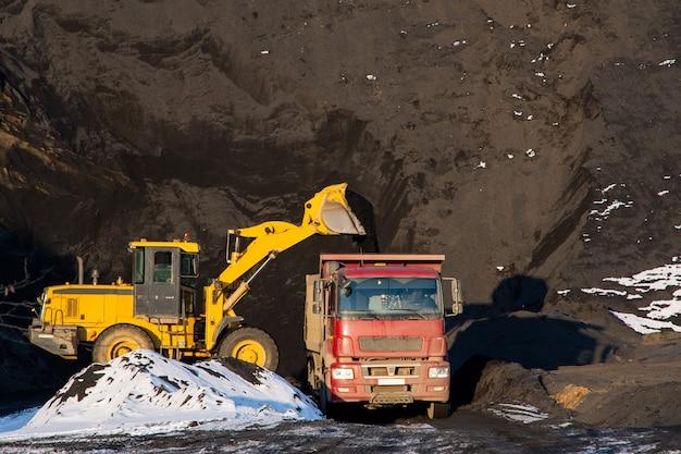 Um trator amarelo carrega um caminhão com escória preta usando um balde em um fundo de montanha preta