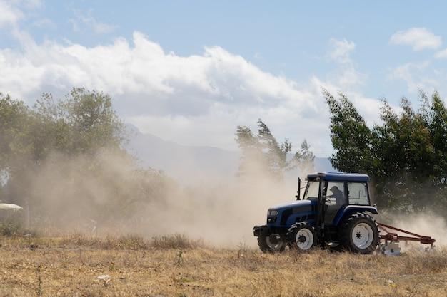 Um trator azul arando um campo em um dia poeirento