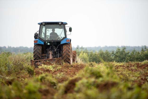 Um trator azul trabalhando em terras agrícolas