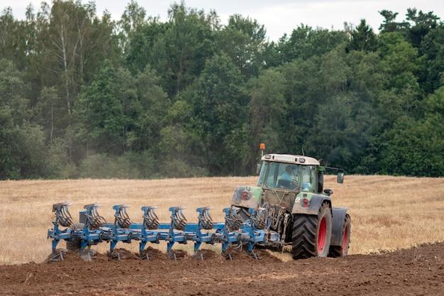 Um trator com arado trata o solo.