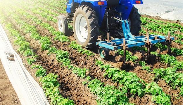 Um trator com um cultivador processa um campo agrícola.