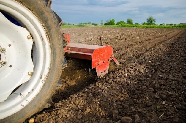 Um trator com uma unidade de corte está cultivando o campo solo úmido e moído após o cultivo