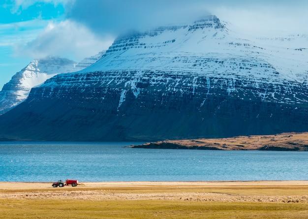 Um trator em um campo com incríveis montanhas nevadas