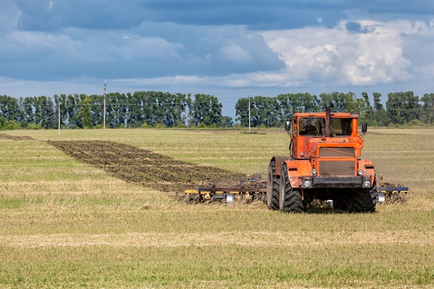 Um trator moderno laranja ara o campo de trigo dourado da terra
