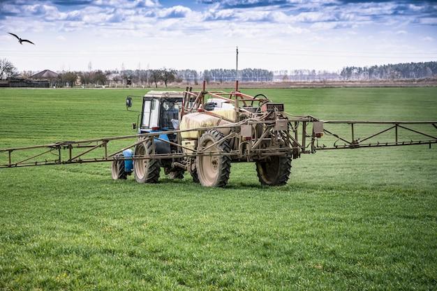 Um trator pulveriza um campo com suplementos de crescimento e destruirá as doenças das plantas. agricultura. fornecimento de comida.