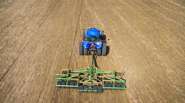 Um trator que ara e semeia no campo