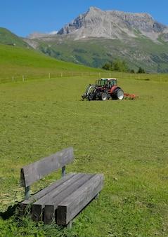 Um trator trabalhando nos campos nas montanhas alpinas da áustria