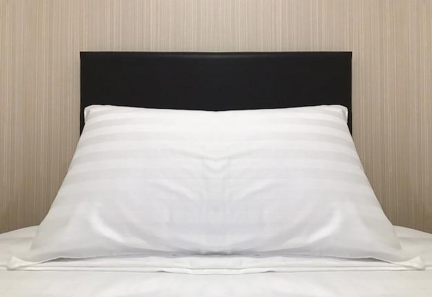 Um travesseiro vazio na cama de solteiro que se prepara para o hóspede.