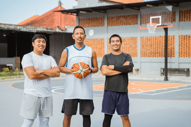 Um treinador e dois jogadores de basquete sorridentes carregando uma bola de basquete