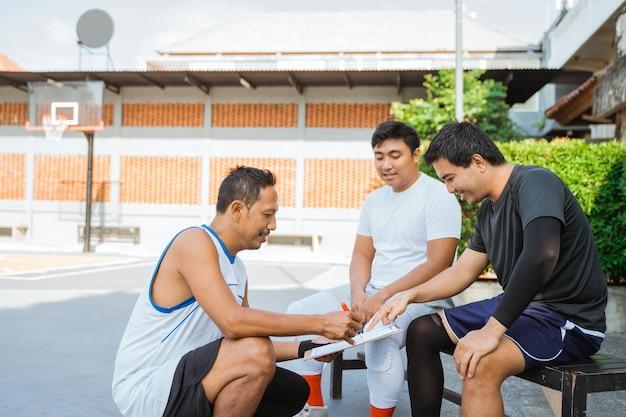 Um treinador segura uma prancheta enquanto instrui dois jogadores de basquete