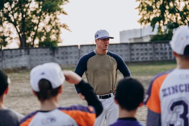 Um treinador sério se comunica com seus alunos ao ar livre