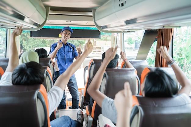 Um tripulante de ônibus masculino uniformizado e com um boné levantado enquanto verifica os passageiros antes de sair para uma viagem de ônibus