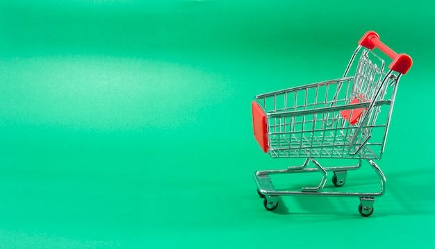 Um trole em um supermercado no fundo verde.