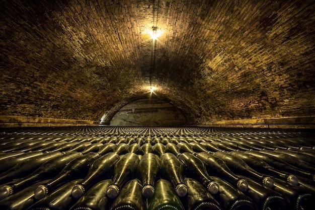 Um túnel de adega com garrafas de vidro