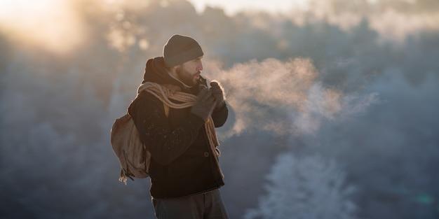 Um turista brutal caminha pela floresta coberta de neve ao amanhecer
