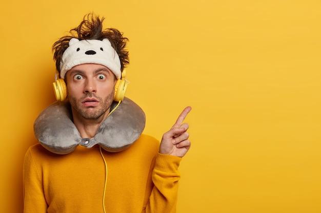 Um turista chocado aponta para longe, mostra algo em um espaço em branco com estupefação, usa uma venda nos olhos e um travesseiro inflado em volta do pescoço