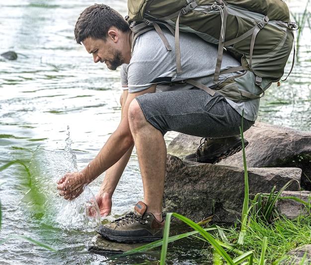 Um turista com uma grande mochila de caminhada perto de um rio de montanha no calor do verão.