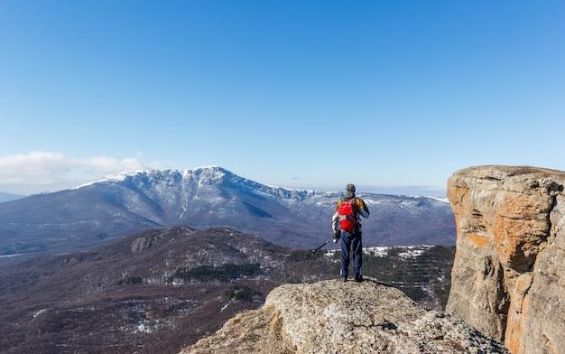 Um turista com uma mochila e varas de turista nas montanhas. turista nas montanhas.