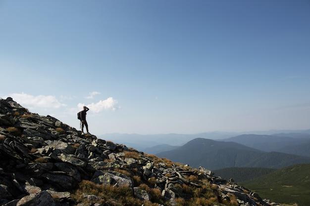 Um turista com uma mochila em uma cadeia de montanhas olha para longe. conceito de viagens de verão