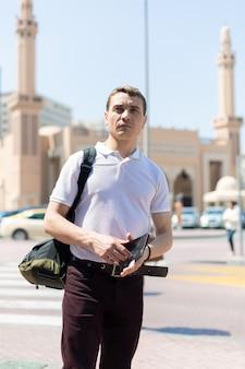 Um turista de 35 a 40 anos com um mapa nas mãos tem como pano de fundo uma mesquita islâmica