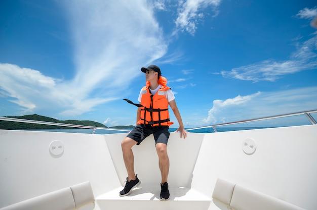 Um turista de colete salva-vidas desfrutando e relaxando em uma lancha com uma bela vista do mar e da montanha