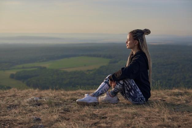 Um turista de esportes garota senta-se na grama seca no topo de uma montanha e olha para a distância contra o ...