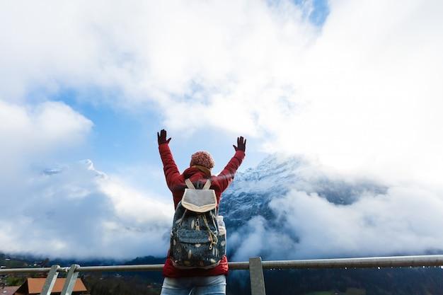 Um turista de mulher excitado enquanto olha para uma montanha alta contra um céu azul nos alpes, suíça