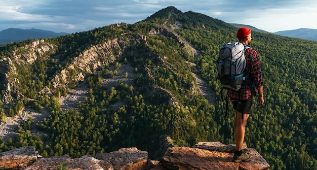 Um turista do sexo masculino com uma mochila admira o pôr do sol do topo da montanha, panorama. um viajante no fundo das montanhas. turista com uma mochila em um fundo de montanha. copie o espaço