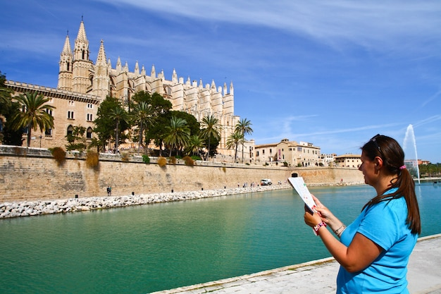Um turista em frente à catedral de palma de maiorca, nas ilhas baleares, espanha
