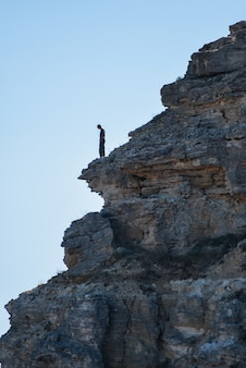 Um turista fica na beira de uma montanha olhando para baixo. viagem de aventura, estilo de vida ativo