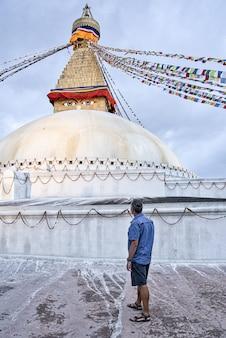 Um turista ocidental com cabelo curto. vestindo camiseta e com as mãos nos bolsos da bermuda, olhando a estupa boudhanath ao pôr do sol na estação das monções.