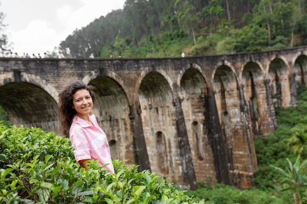Um turista posa em uma plantação de chá perto da famosa ponte de nove arcos no sri lanka. turismo em lugares pitorescos
