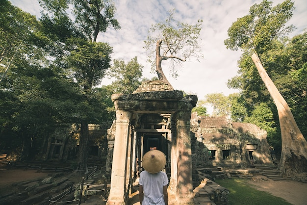Um turista que visita ruínas de angkor em meio a selva