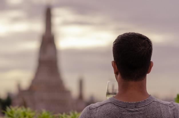 Um turista segurando um copo de vinho branco olhando turva do templo.
