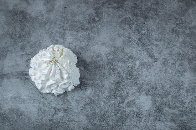 Um único biscoito de merengue branco isolado no chão.