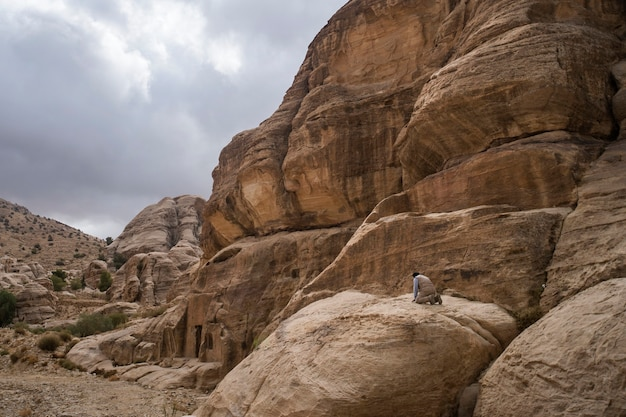 Um único homem se ajoelha durante sua oração diária nas montanhas do jordão. a mundialmente famosa cidade de petra jordan. oração ao ar livre na natureza.