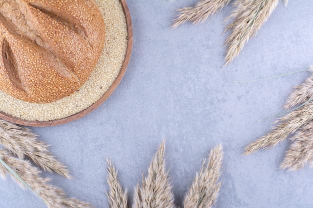 Um único pedaço de pão em uma bandeja cheia de sementes de gergelim, cercado por hastes de grama seca na superfície de mármore