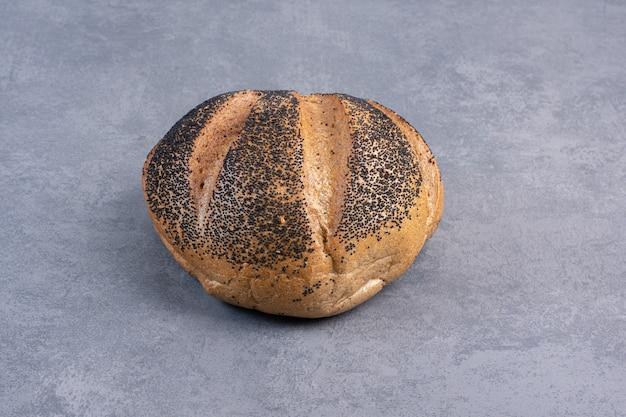 Um único pedaço de pão revestido de gergelim preto sobre mármore.
