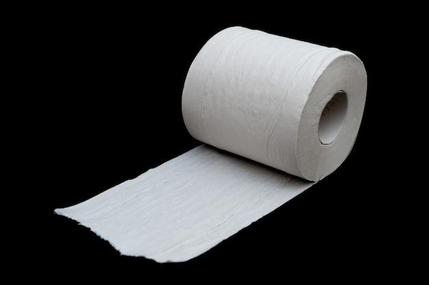 Um único rolo de papel higiênico branco desenrolado isolado em um fundo preto