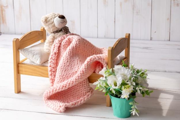 Um ursinho de pelúcia está deitado em uma pequena cama de madeira, coberto com um cobertor de tricô. ao lado dela está um vaso com uma flor artificial. conceito de sono de bebê