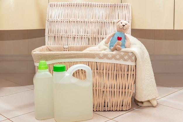 Um ursinho de pelúcia está sentado no cesto de roupa suja no banheiro ao lado do detergente e abrilhantador.