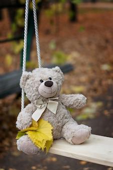 Um ursinho de pelúcia teddy senta-se em um balanço