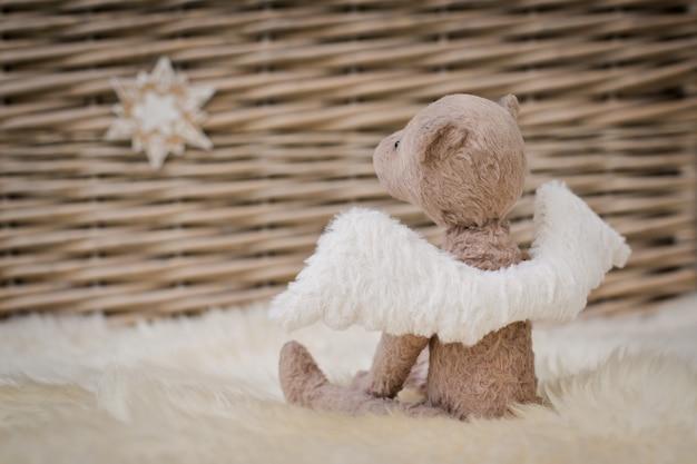 Um urso de peluche com asas do anjo senta-se no fundo de uma cesta de vime.