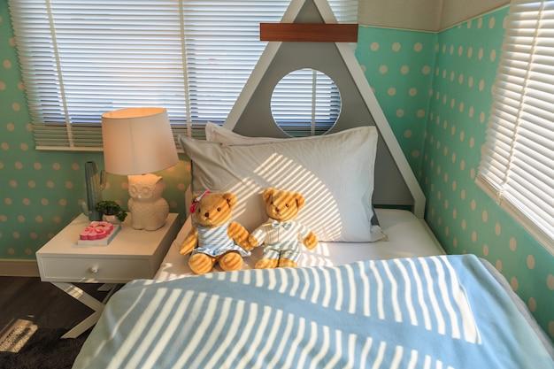 Um urso de peluche marrom do par que inclina o descanso branco na cama.
