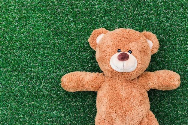 Um urso de pelúcia em um fundo de grama verde