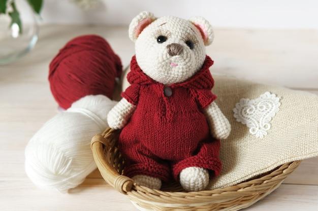 Um urso feito de fios de lã. brinquedo de pelúcia de malha artesanal sobre uma mesa de madeira.