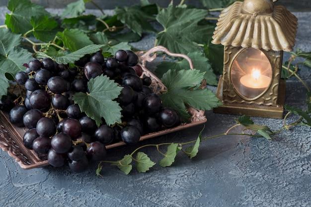 Um uvas escuras em um vaso de bronze e um castiçal de ouro com uma vela