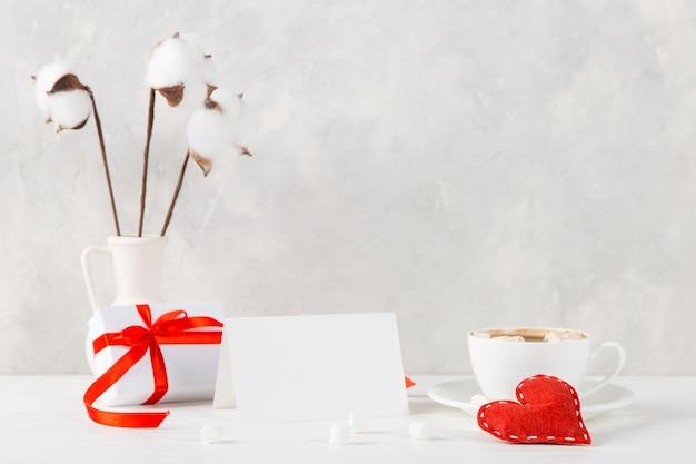 Um vaso com algodão, coração vermelho, café da manhã e um presente contra a parede de luz, conceito, um postal de dia dos namorados