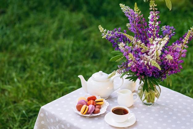 Um vaso com flores de tremoço, um bule de chá e uma xícara de chá em uma bandeja de madeira