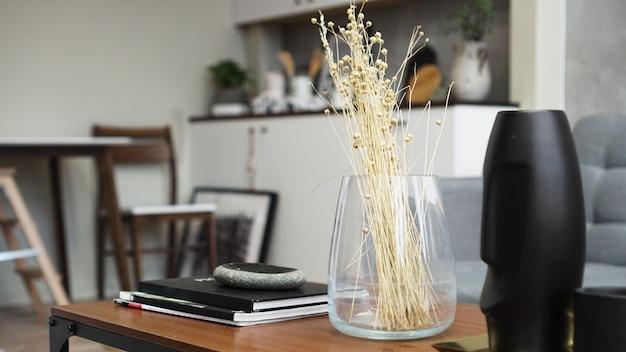 Um vaso com flores secas sobre uma mesa. quarto clássico escandinavo com detalhes em madeira e branco, design interior minimalista. foto real. casa aconchegante.